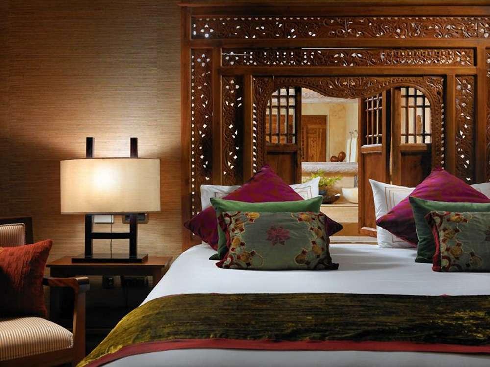 Много разноцветных подушек - фишка интерьера спальни в этническом стиле